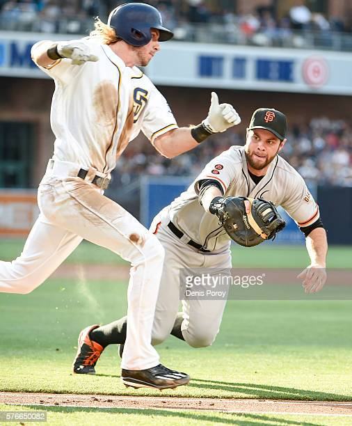 Brandon Belt of the San Francisco Giants dives as he makes the tag on Travis Jankowski of the San Diego Padres during the second inning of a baseball...