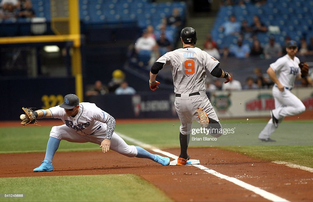Brandon Belt #9 of the San Francisco Giants gets safely to first base ahead of first baseman Logan Morrison #7 of the Tampa Bay Rays off of his single during the first inning of a game on June 19, 2016 at Tropicana Field in St. Petersburg, Florida.