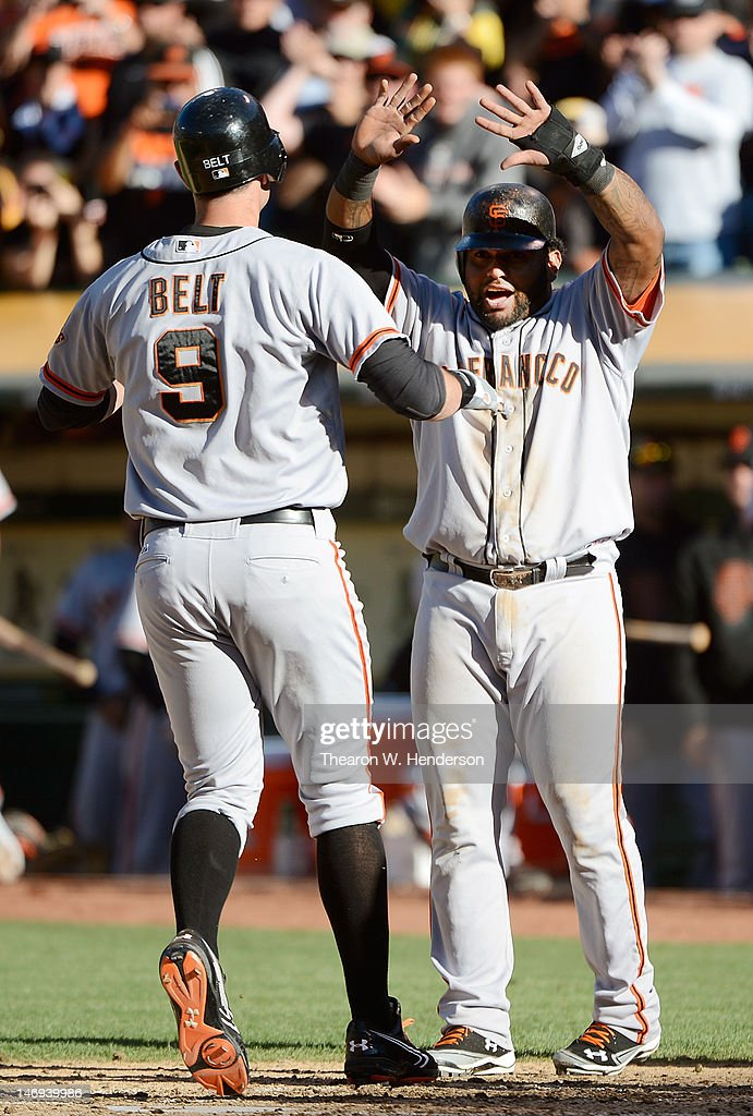 <a gi-track='captionPersonalityLinkClicked' href=/galleries/search?phrase=Brandon+Belt&family=editorial&specificpeople=7513394 ng-click='$event.stopPropagation()'>Brandon Belt</a> #9 of the San Francisco Giants is congratulated at home plate by <a gi-track='captionPersonalityLinkClicked' href=/galleries/search?phrase=Pablo+Sandoval&family=editorial&specificpeople=803207 ng-click='$event.stopPropagation()'>Pablo Sandoval</a> #48 who scored in front of Belt on a two-run home run in the six inning against the Oakland Athletics at O.co Coliseum on June 23, 2012 in Oakland, California.
