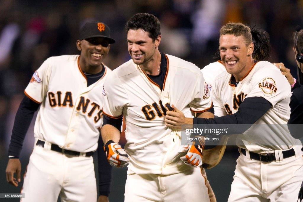 <a gi-track='captionPersonalityLinkClicked' href=/galleries/search?phrase=Brandon+Belt&family=editorial&specificpeople=7513394 ng-click='$event.stopPropagation()'>Brandon Belt</a> #9 of the San Francisco Giants is congratulated by Joaquin Arias (L) and <a gi-track='captionPersonalityLinkClicked' href=/galleries/search?phrase=Hunter+Pence&family=editorial&specificpeople=757341 ng-click='$event.stopPropagation()'>Hunter Pence</a> (R) after hitting a walk-off single against the Colorado Rockies during the tenth inning at AT&T Park on September 9, 2013 in San Francisco, California. The Giants defeated the Rockies 3-2 in 10 innings.