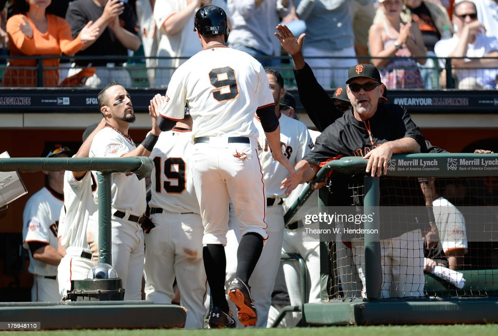 Brandon Belt of the San Francisco Giants is congratulated by manager Bruce Bochy and Andres Torres after Belt scored in the six inning against the...