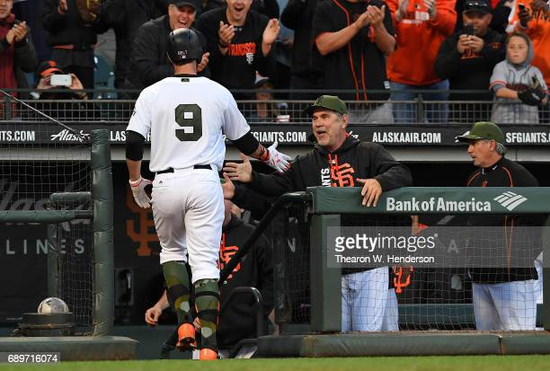Brandon Belt of the San Francisco Giants is congratulated by manager Bruce Bochy after Belt hit a solo home run against the Atlanta Braves in the...