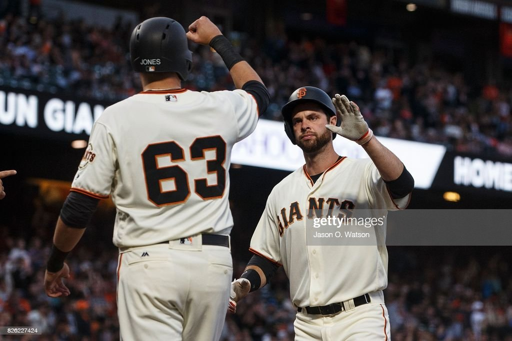 Brandon Belt #9 of the San Francisco Giants is congratulated by Ryder Jones #63 after hitting a two run home run against the Oakland Athletics during the second inning at AT&T Park on August 3, 2017 in San Francisco, California. The San Francisco Giants defeated the Oakland Athletics 11-2.