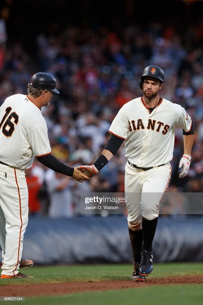 Brandon Belt #9 of the San Francisco Giants is congratulated by third base coach Phil Nevin #16 after hitting a two run home run against the Oakland Athletics during the second inning at AT&T Park on August 3, 2017 in San Francisco, California. The San Francisco Giants defeated the Oakland Athletics 11-2.
