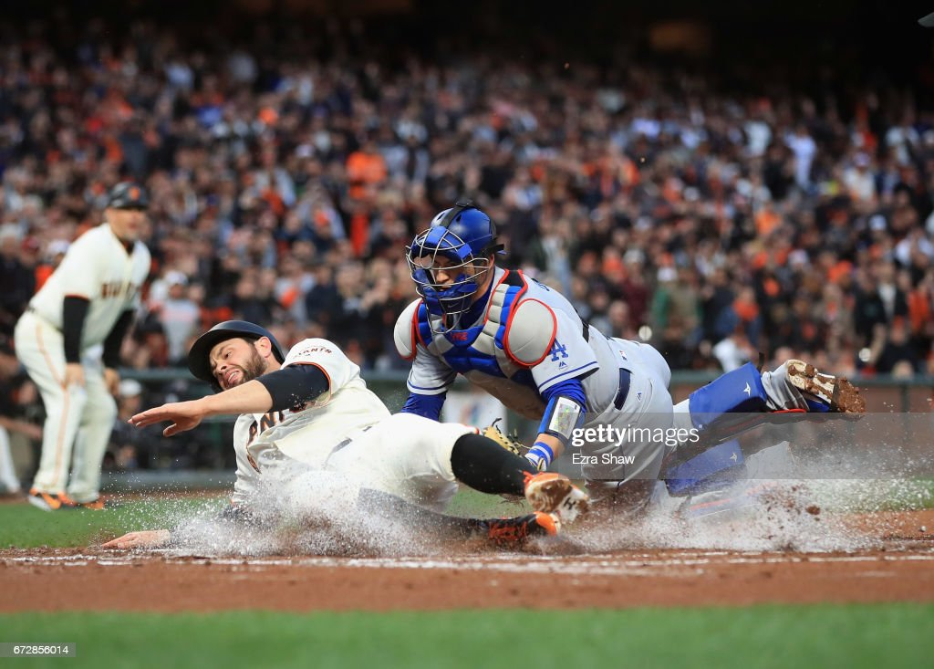Brandon Belt #9 of the San Francisco Giants is tagged out by Yasmani Grandal #9 of the Los Angeles Dodgers in the first inning at AT&T Park on April 24, 2017 in San Francisco, California.