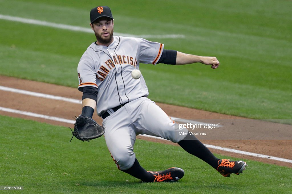 Brandon Belt #9 of the San Francisco Giants makes a sliding catch to retire Wily Peralta of the Milwaukee Brewers during the fourth inningon Opening Day at Miller Park on April 04, 2016 in Milwaukee, Wisconsin.