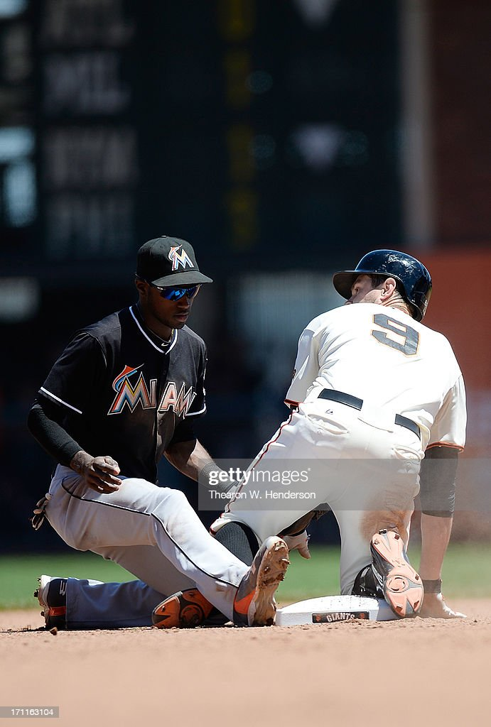 Brandon Belt #9 of the San Francisco Giants slides into second base safe with a double, beating the tag of Adeiny Hechavarria #3 of the Miami Marlins in the fourth inning at AT&T Park on June 22, 2013 in San Francisco, California.