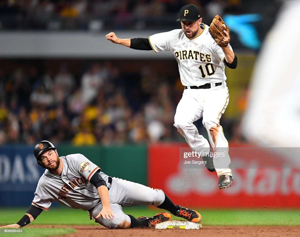 Brandon Belt #9 of the San Francisco Giants slides safely into second base in front of Jordy Mercer #10 of the Pittsburgh Pirates during the sixth inning at PNC Park on June 30, 2017 in Pittsburgh, Pennsylvania.