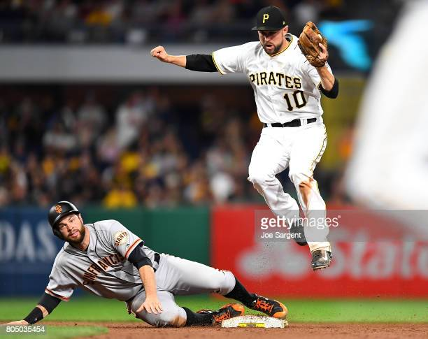 Brandon Belt of the San Francisco Giants slides safely into second base in front of Jordy Mercer of the Pittsburgh Pirates during the sixth inning at...