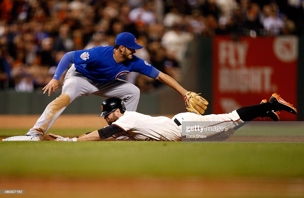 Brandon Belt #9 of the San Francisco Giants slides under the tag of Kris Bryant #17 of the Chicago Cubs for a triple in the sixth inning at AT&T Park on August 26, 2015 in San Francisco, California.