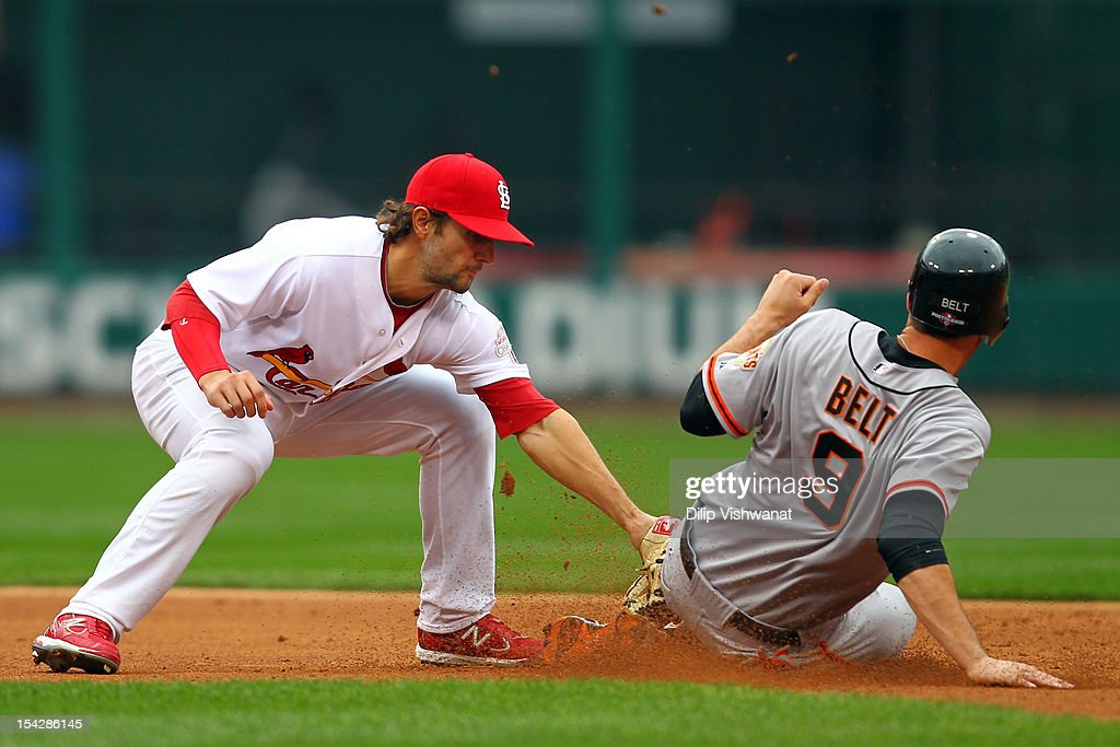 Brandon Belt #9 of the San Francisco Giants slides under the tag of Pete Kozma #38 of the St. Louis Cardinals and is safe in the second inning in Game Three of the National League Championship Series at Busch Stadium on October 17, 2012 in St Louis, Missouri.