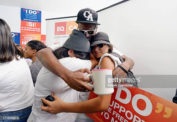 Brandon Benoit hugs Martha Acevedo and Briana Castaneda as they celebrate the Supreme Court ruling at a watch party at Equality California a...