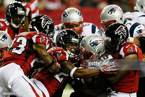 Brandon Bolden of the New England Patriots is tackled by Robert Alford Robert McClain and Akeem Dent of the Atlanta Falcons during the game at...