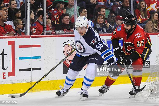 Brandon Bollig of the Calgary Flames chases Marko Dano of the Winnipeg Jets during an NHL game at Scotiabank Saddledome on March 16 2016 in Calgary...