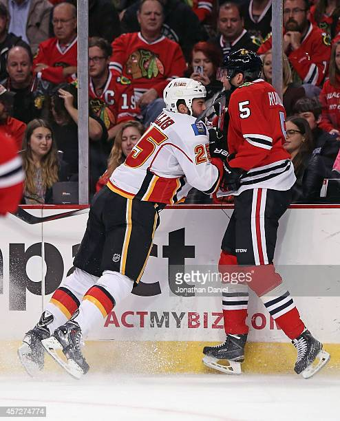 Brandon Bollig of the Calgary Flames checks David Rundblad of the Chicago Blackhawks at the United Center on October 15 2014 in Chicago Illinois