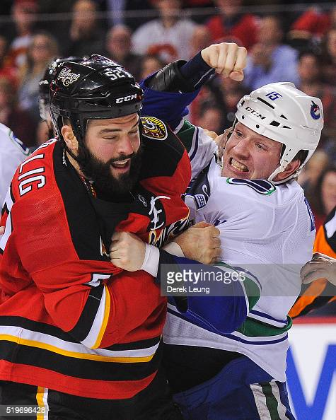 Brandon Bollig of the Calgary Flames fights Derek Dorsett of the Vancouver Canucks during an NHL game at Scotiabank Saddledome on April 7 2016 in...