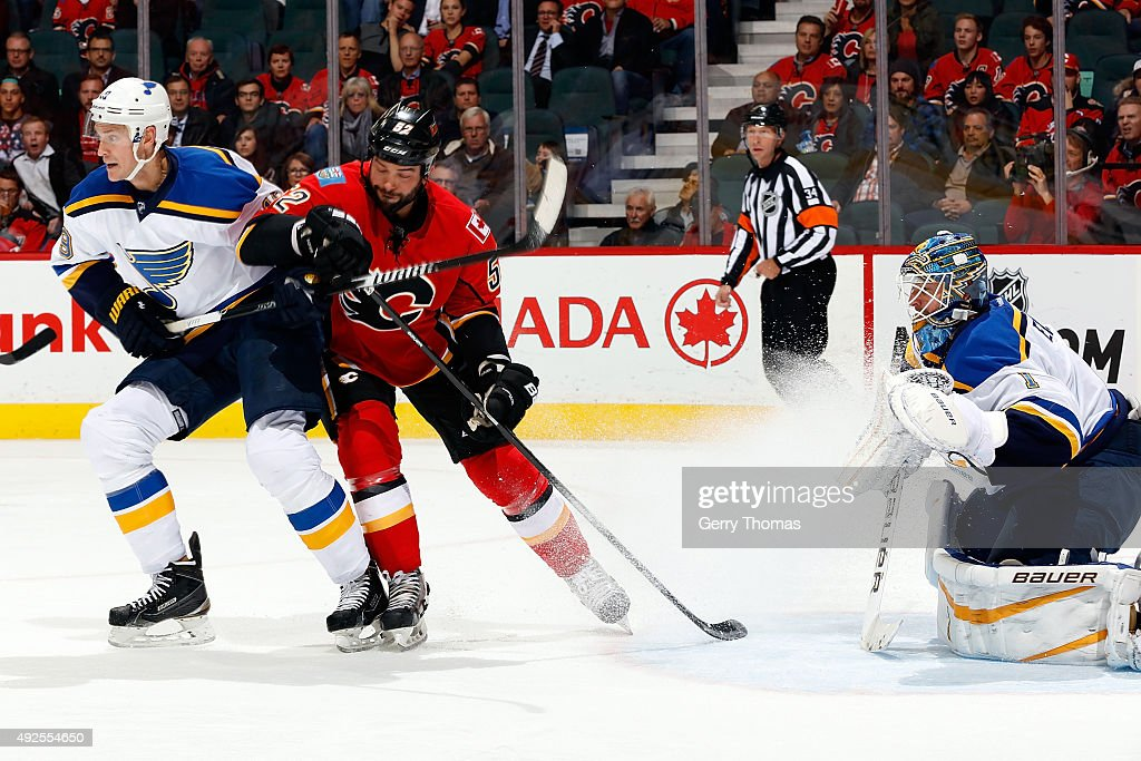 Brandon Bollig #52 of the Calgary Flames skates against Jay Bouwmeester #19 and Brian Elliot #1 of the St. Louis Blues during an NHL game at Scotiabank Saddledome on October 13, 2015 in Calgary, Alberta, Canada.