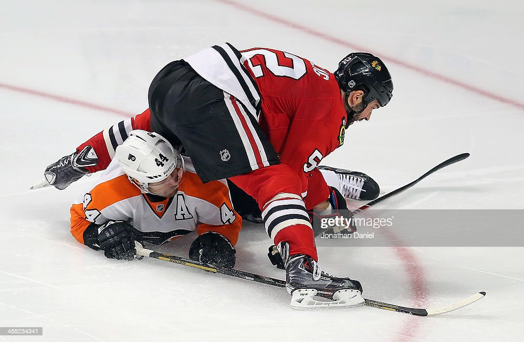 <a gi-track='captionPersonalityLinkClicked' href=/galleries/search?phrase=Brandon+Bollig&family=editorial&specificpeople=7186858 ng-click='$event.stopPropagation()'>Brandon Bollig</a> #52 of the Chicago Blackhawks lands on top of <a gi-track='captionPersonalityLinkClicked' href=/galleries/search?phrase=Kimmo+Timonen&family=editorial&specificpeople=201521 ng-click='$event.stopPropagation()'>Kimmo Timonen</a> #44 of the Philadelphia Flyers after tsking a shot at the United Center on December 11, 2013 in Chicago, Illinois. The Blackhawks defeated the Flyers 7-2.