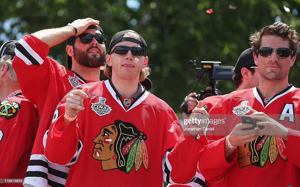 Brandon Bollig #52, Patrick Kane #88 and Patrick Sharp #10 of the Chicago Blackhawks enjoy the ceremony during the Blackhawks Victory Parade and Rally on June 28, 2013 in Chicago, Illinois.