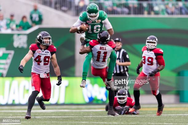 Brandon Bridge of the Saskatchewan Roughriders tries to hurdle Joshua Bell of the Calgary Stampeders after scrambling with the ball in the second...