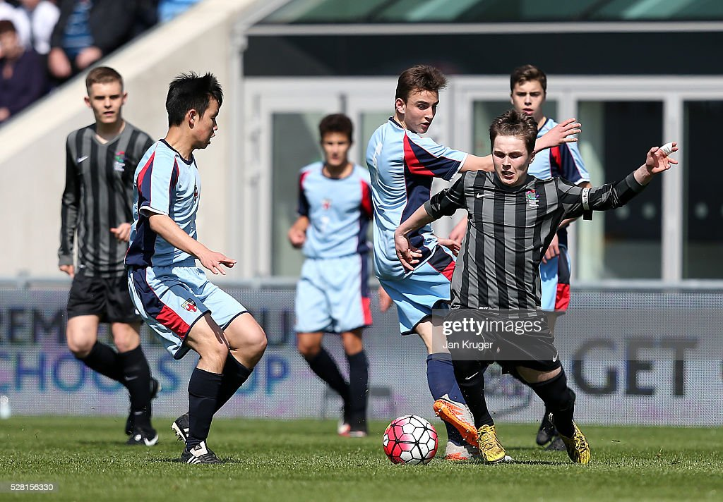 Brandon Burrows of Blacon High School battles with Yahoo Ho of King Edwards's School Witley during the Premier League under 16 Small Schools' Cup final match between King Edwards's School Witley and Blacon High School at the Academy Training Ground on May 04, 2016 in Manchester, England.