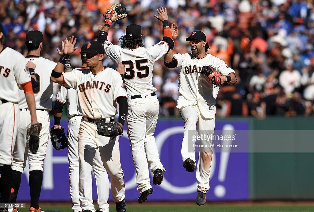 Brandon Crawford #35, Angel Pagan #16 and teammates of the San Francisco Giants celebrates defeating the Los Angeles Dodgers 3-0 at AT&T Park on October 1, 2016 in San Francisco, California.