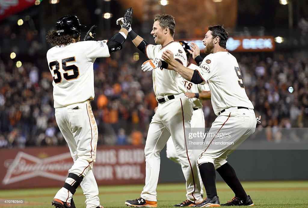 <a gi-track='captionPersonalityLinkClicked' href=/galleries/search?phrase=Brandon+Crawford&family=editorial&specificpeople=5580312 ng-click='$event.stopPropagation()'>Brandon Crawford</a> #35, <a gi-track='captionPersonalityLinkClicked' href=/galleries/search?phrase=Joe+Panik&family=editorial&specificpeople=9008902 ng-click='$event.stopPropagation()'>Joe Panik</a> #12 and <a gi-track='captionPersonalityLinkClicked' href=/galleries/search?phrase=Brandon+Belt&family=editorial&specificpeople=7513394 ng-click='$event.stopPropagation()'>Brandon Belt</a> #9 of the San Francisco Giants celebrates after Panik hit a sacrifice fly to score the winning run against the Los Angeles Dodgers in the bottom of the ninth inning at AT&T Park on April 22, 2015 in San Francisco, California. The Giants won the game 3-2.