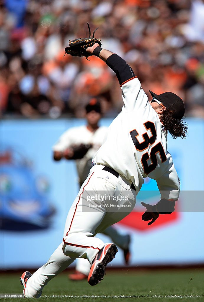 Brandon Crawford #35 of the San Francisco Giants catches a foul pop-up over his shoulder off the bat of Adeny Hechavarria #3 of the Miami Marlins in the ninth inning at AT&T Park on June 22, 2013 in San Francisco, California.