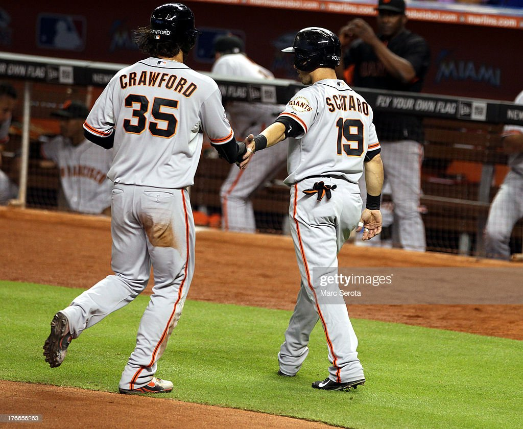 <a gi-track='captionPersonalityLinkClicked' href=/galleries/search?phrase=Brandon+Crawford&family=editorial&specificpeople=5580312 ng-click='$event.stopPropagation()'>Brandon Crawford</a> #35 of the San Francisco Giants celebrates scoring a run with teammate <a gi-track='captionPersonalityLinkClicked' href=/galleries/search?phrase=Marco+Scutaro&family=editorial&specificpeople=239523 ng-click='$event.stopPropagation()'>Marco Scutaro</a> #19 against the Miami Marlins during the first inning at Marlins Park on August 16, 2013 in Miami, Florida.