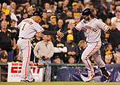 Brandon Crawford of the San Francisco Giants celebrates with third base coach Tim Flannery as he rounds the bases after hitting a fourrun home run in...