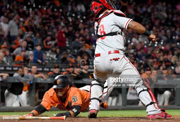Brandon Crawford of the San Francisco Giants dives into home plate and scores as the ball is thrown past catcher Jorge Alfaro of the Philadelphia...
