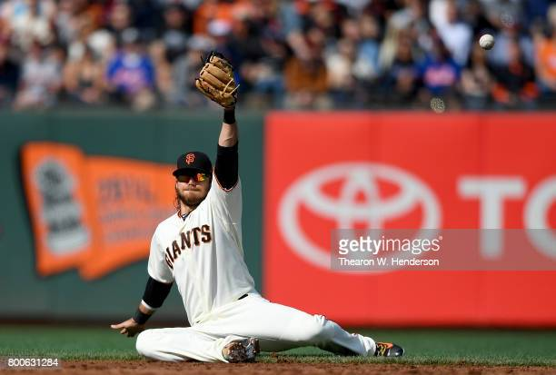 Brandon Crawford of the San Francisco Giants falls to the ground and watches the ball kick over the top of his glove for a single off the bat of...