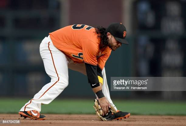 Brandon Crawford of the San Francisco Giants goes down to field a ground ball off the bat of Stephen Piscotty of the St Louis Cardinals in the top of...