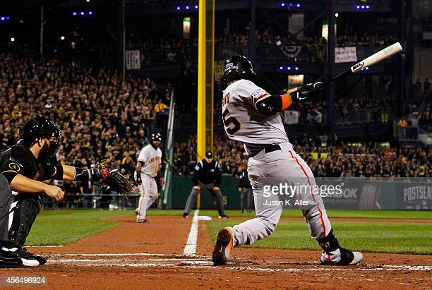 Brandon Crawford of the San Francisco Giants hits a fourrun home run in the fourth inning against the Pittsburgh Pirates during the National League...