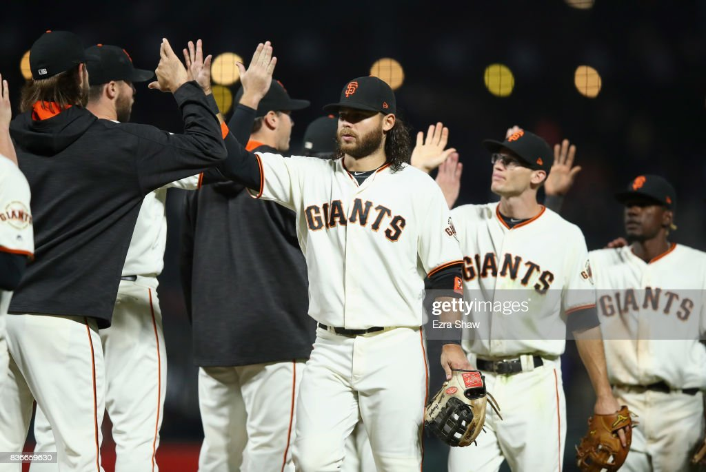 Brandon Crawford #35 of the San Francisco Giants is congratulated by teammates after they beat the Milwaukee Brewers at AT&T Park on August 21, 2017 in San Francisco, California.