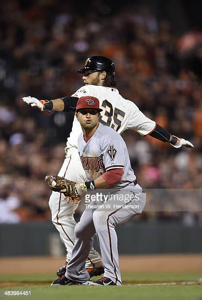 Brandon Crawford of the San Francisco Giants is out on a fielder's choice at third base by Martin Prado of the Arizona Diamondbacks in the bottom of...