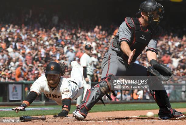Brandon Crawford of the San Francisco Giants scores on a throwing error by pitcher Taijuan Walker of the Arizona Diamondbacks to catcher Jeff Mathis...