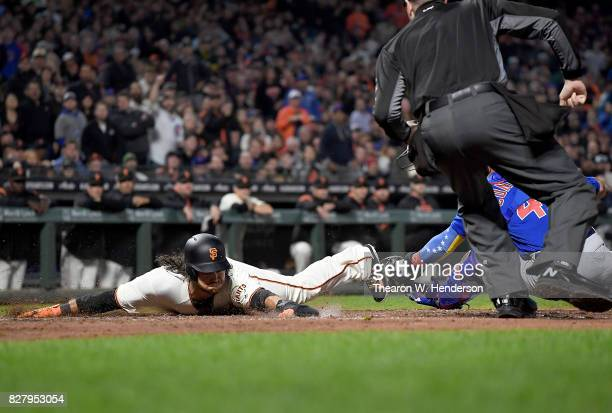 Brandon Crawford of the San Francisco Giants scores sliding around the tag of Willson Contreras of the Chicago Cubs in the bottom of the fourth...