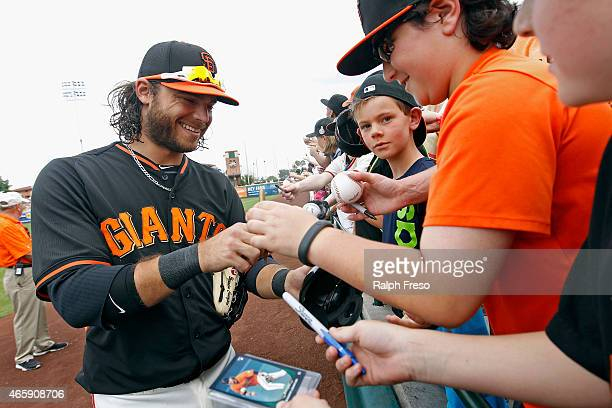 Brandon Crawford of the San Francisco Giants signs autographs for fans before the start of a Cactus League game against the Milwaukee Brewers at...