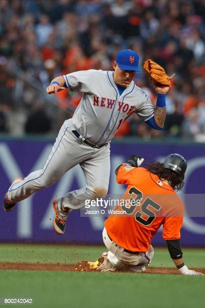 Brandon Crawford of the San Francisco Giants slides into second base to break up a double play attempt by Asdrubal Cabrera of the New York Mets...