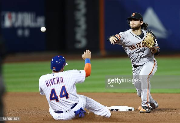 Brandon Crawford of the San Francisco Giants turns a double play as Rene Rivera of the New York Mets slides into second base in the third inning...