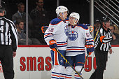 Brandon Davidson of the Edmonton Oilers is congratulated by teammate Andrew Miller after scoring against the Colorado Avalanche at the Pepsi Center...