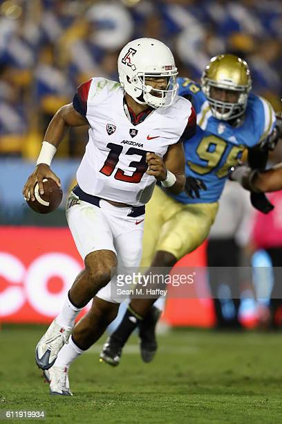 Brandon Dawkins of the Arizona Wildcats scrambles to avoid Takkarist McKinley of the UCLA Bruins during the first half of a game at the Rose Bowl on...
