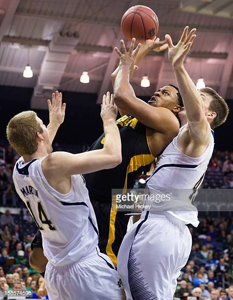 Brandon Dawson of the Kennesaw State Owls shoots the ball against Scott Martin of the Notre Dame Fighting Irish at Purcel Pavilion on December 19...