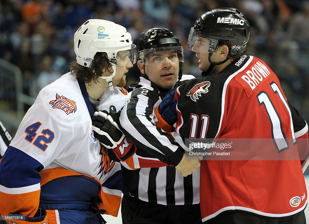 Brandon DeFazio #42 of the Bridgeport Sound Tigers and Chris Brown #11 of the Portland Pirates are separated by the referee during an American Hockey League game on January 12, 2013 at the Webster Bank Arena at Harbor Yard in Bridgeport, Connecticut.