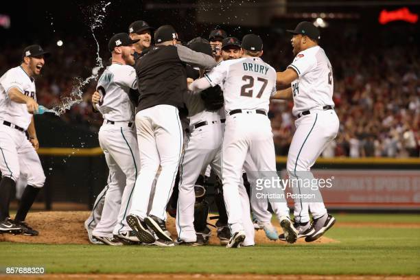 Brandon Drury and Yasmany Tomas of the Arizona Diamondbacks celebrate with teammates after defeating the Colorado Rockies 118 in the National League...
