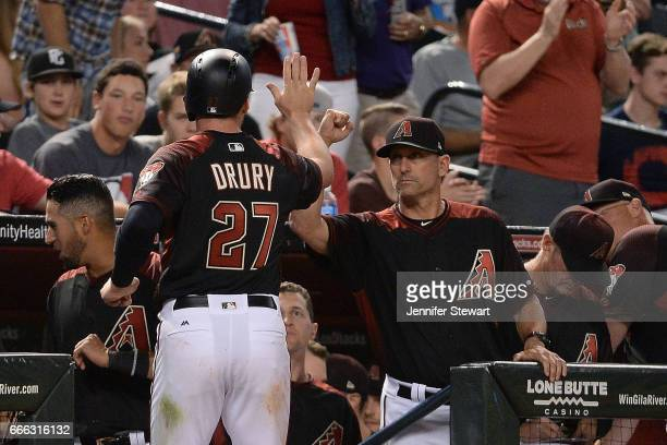 Brandon Drury of the Arizona Diamondbacks is high fived by manager Torey Lovullo after scoring against the Cleveland Indians in the sixth inning at...