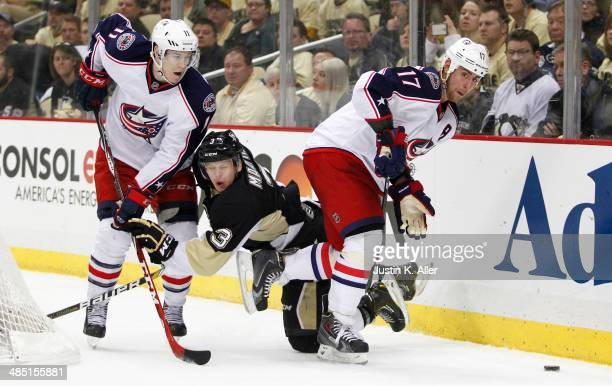 Brandon Dubinsky and Matt Calvert of the Columbus Blue Jackets battle behind the net against Olli Maatta of the Pittsburgh Penguins in Game One of...
