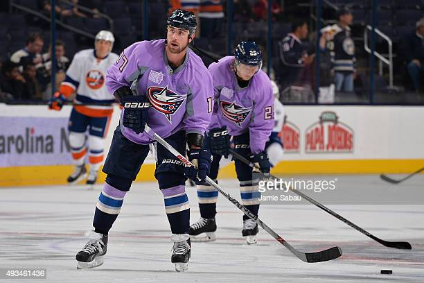 Brandon Dubinsky and William Karlsson of the Columbus Blue Jackets sport purple jerseys for Hockey Fights Cancer night during warmups prior to a game...