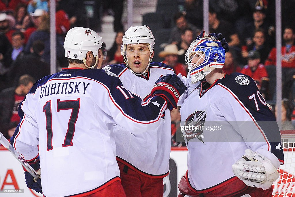 Brandon Dubinsky #17, Jack Johnson #7, and Joonas Korpisalo #70 of the Columbus Blue Jackets celebrate after defeating the Calgary Flames during an NHL game at Scotiabank Saddledome on February 5, 2016 in Calgary, Alberta, Canada.